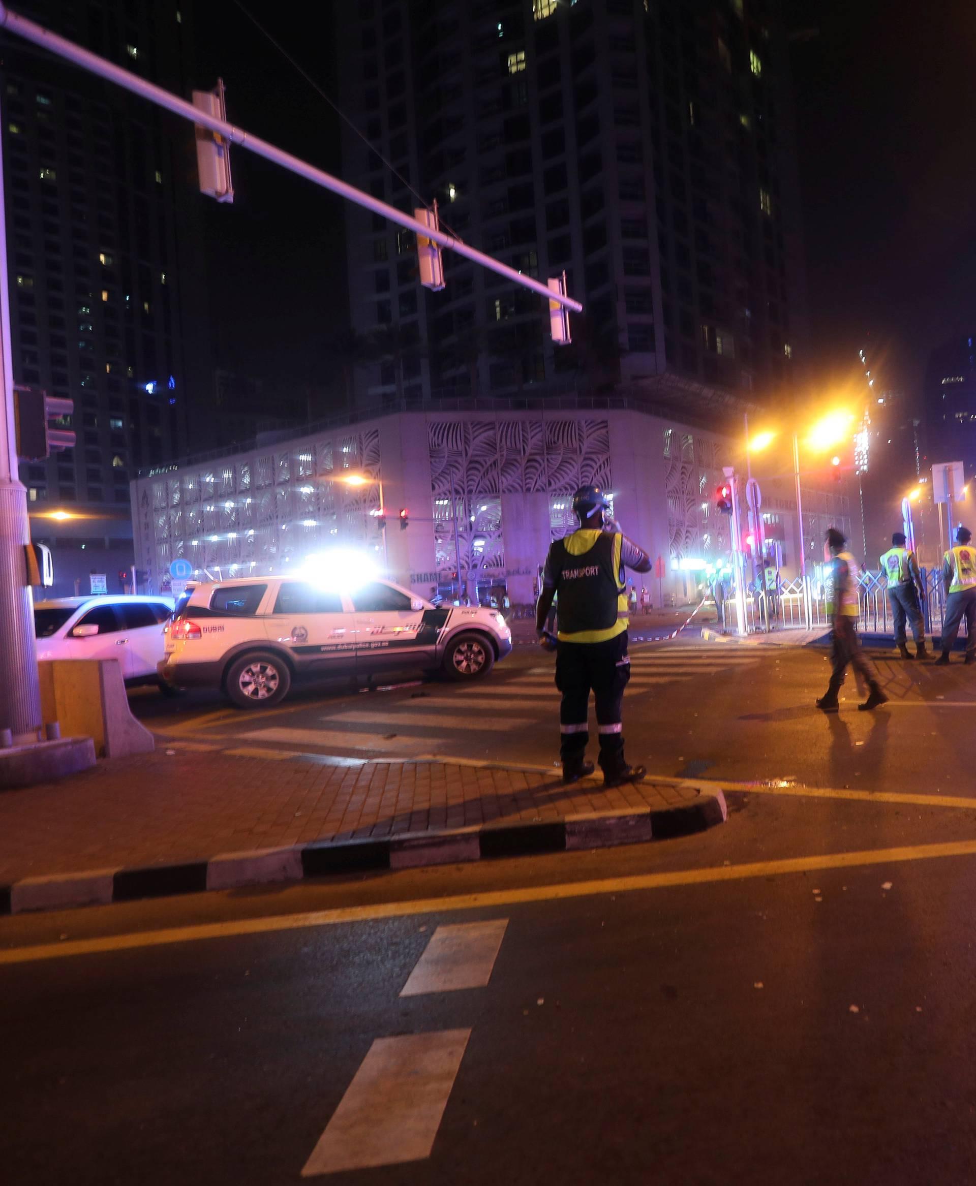 Dubai Emergency Response teams and Dubai police are seen on the street near Dubai's Torch tower residential building in the Marina district, Dubai