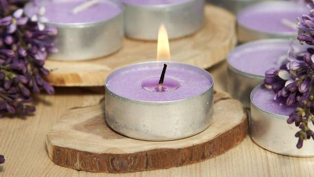 Scented candles on a wooden stand with lilac flowers on the tabl