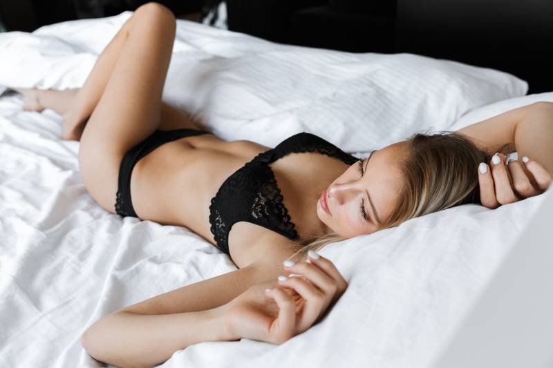 Image of young woman 20s wearing luxury lingerie smiling, while