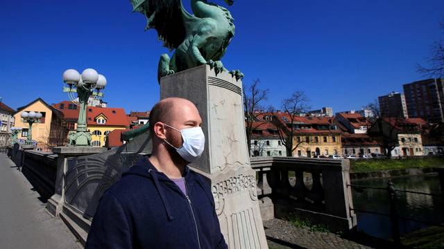 FILE PHOTO: A man with a face mask walks on the Dragon's bridge during coronavirus disease (COVID-19) fears, in Ljubljana