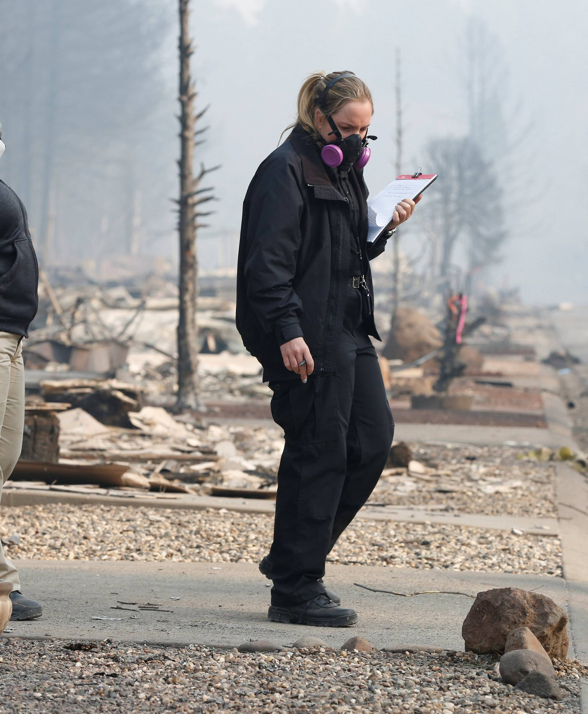 Marin County Forensic Technician Alexandra Torres (L) and San Mateo County Deputy Coroner Elizabeth Ortiz recover human remains from a trailer home destroyed by the Camp Fire in Paradise