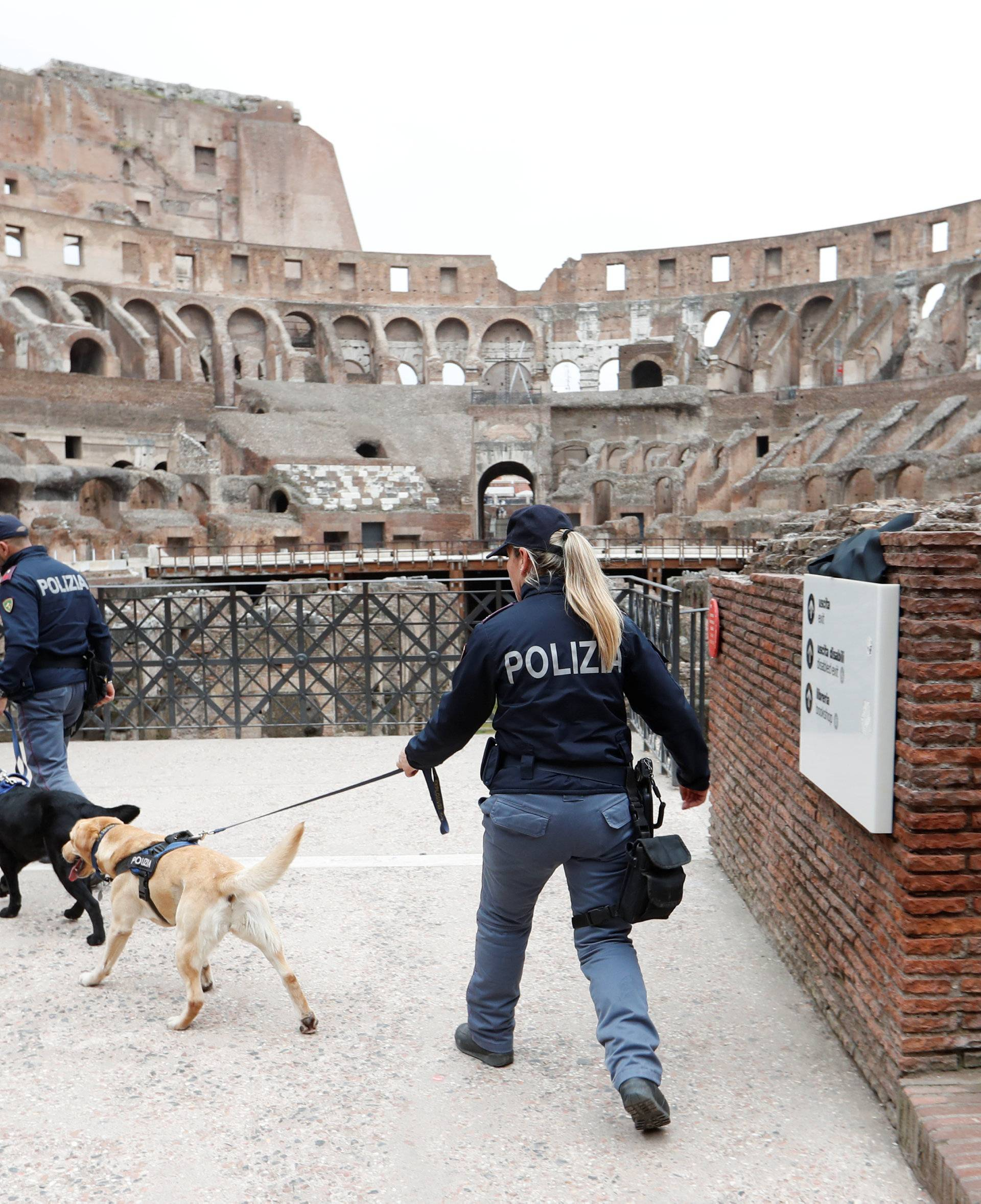 Security patrol with dogs inside the Colosseum before the Via Crucis (Way of the Cross) procession during Good Friday celebrations in Rome