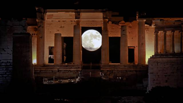 """A rising """"supermoon"""" is seen through the Propylaea, the ancient Acropolis hill gateway, in Athens"""