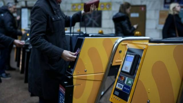 A passenger swipes a card against a terminal to ride the subway system in Kiev