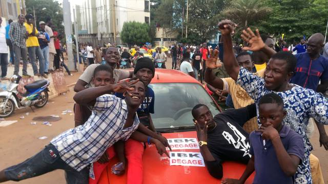 Opposition supporters react to the news of possible military mutiny, at Independence Square in Bamako