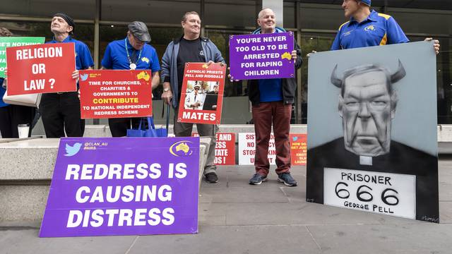 Protesters of Cardinal George Pell are seen outside the County Court in Melbourne