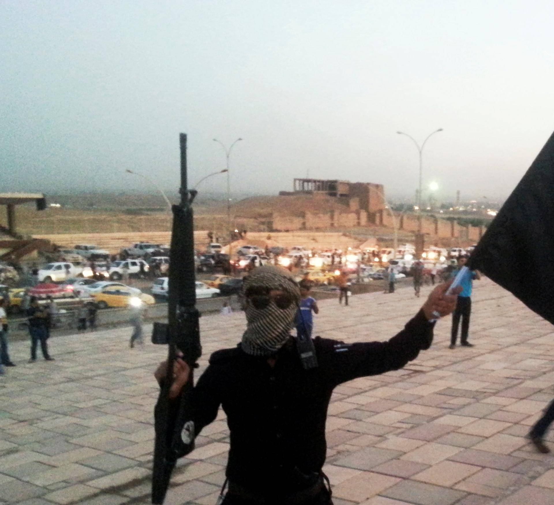 FILE PHOTO: A fighter of the ISIL holds a flag and a weapon on a street in Mosul