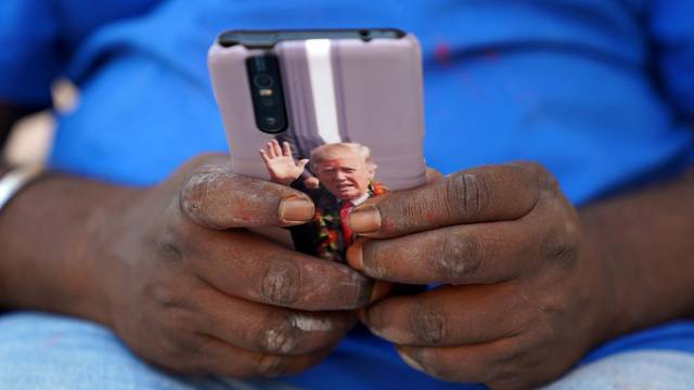 FILE PHOTO: Bussa Krishna, a fan of U.S. President Donald Trump, checks his mobile phone with an image of Trump outside his house in Konney village