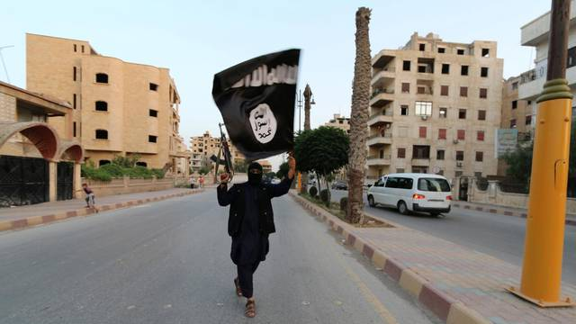 FILE PHOTO - A member loyal to the Islamic State in Iraq and the Levant (ISIL) waves an ISIL flag in Raqqa