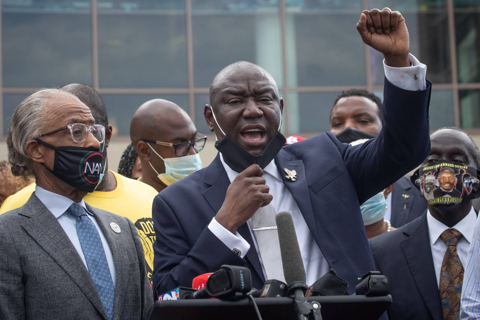 Attorney Ben Crump raises his arm while addressing media  during the public viewing for Floyd at The Fountain of Praise church in Houston