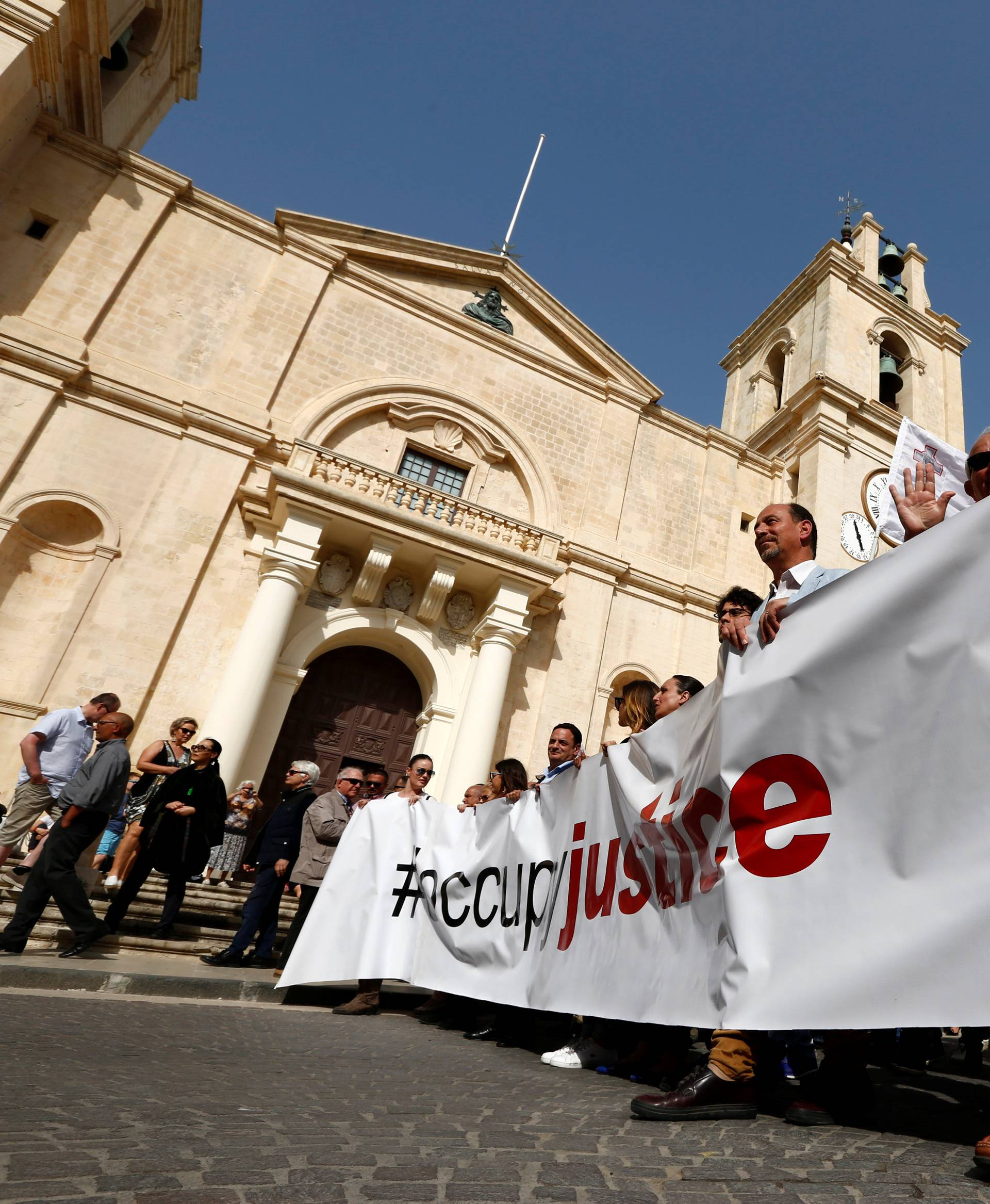 Demonstrators carry a banner during a protest against government corruption in light of the revelations in the Daphne Project, in Valletta