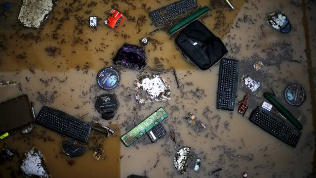 Keyboards and office supplies are seen in a street after floods in Santiago