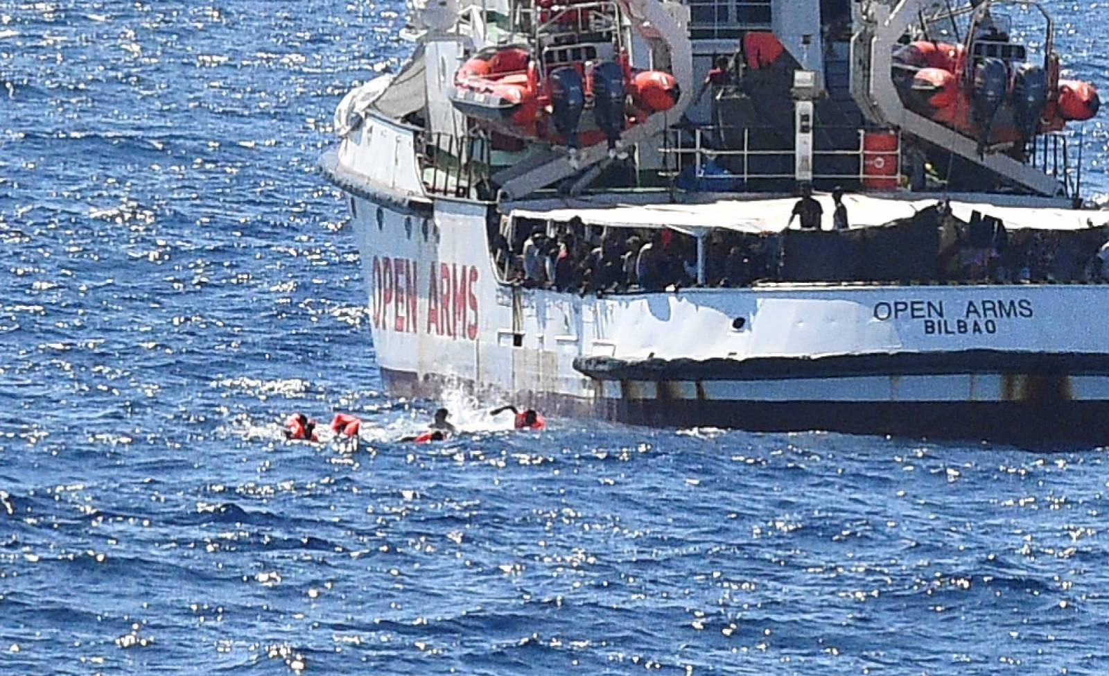 Migrants jump off the Spanish rescue ship Open Arms, close to the Italian shore in Lampedusa