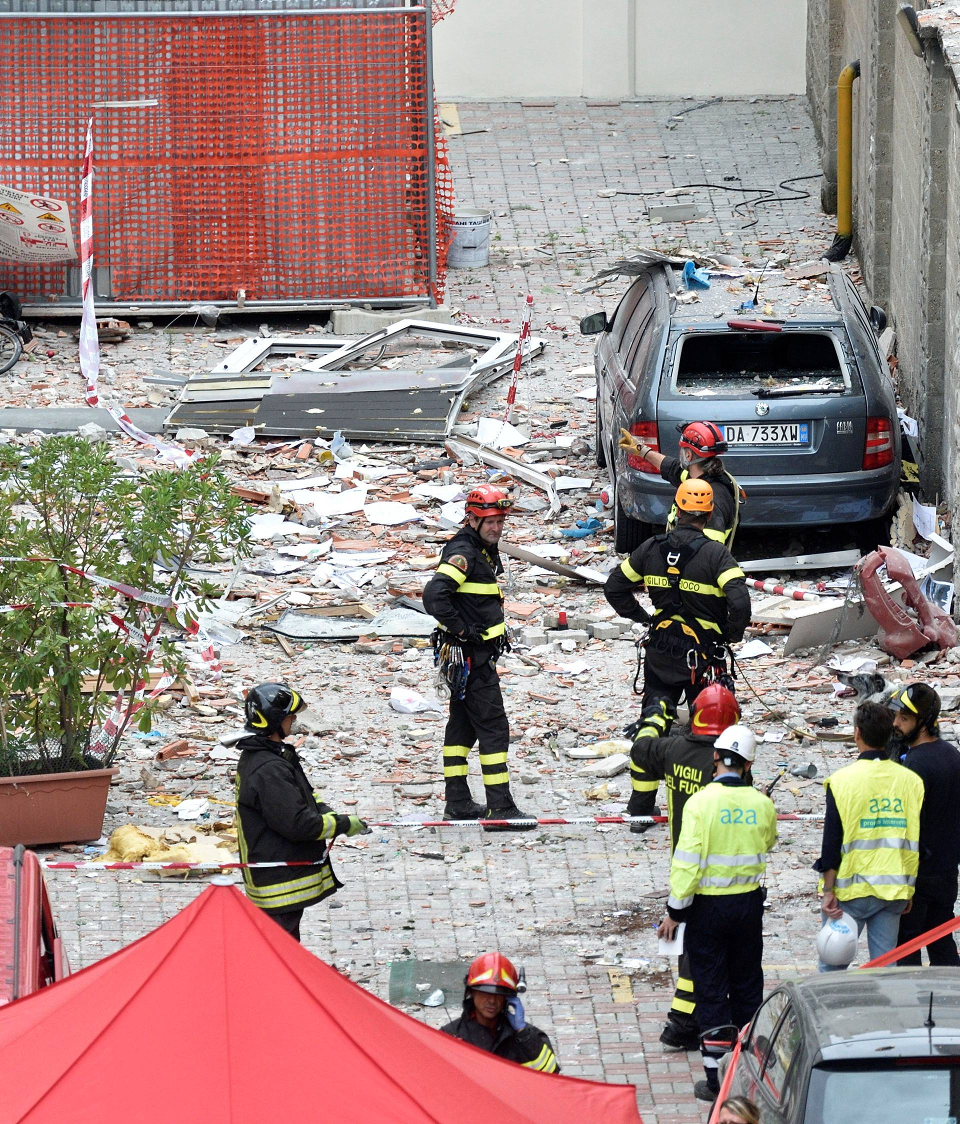 Italian firefighters work in the debris after a residential building partially collapsed on Sunday following an explosion in Milan