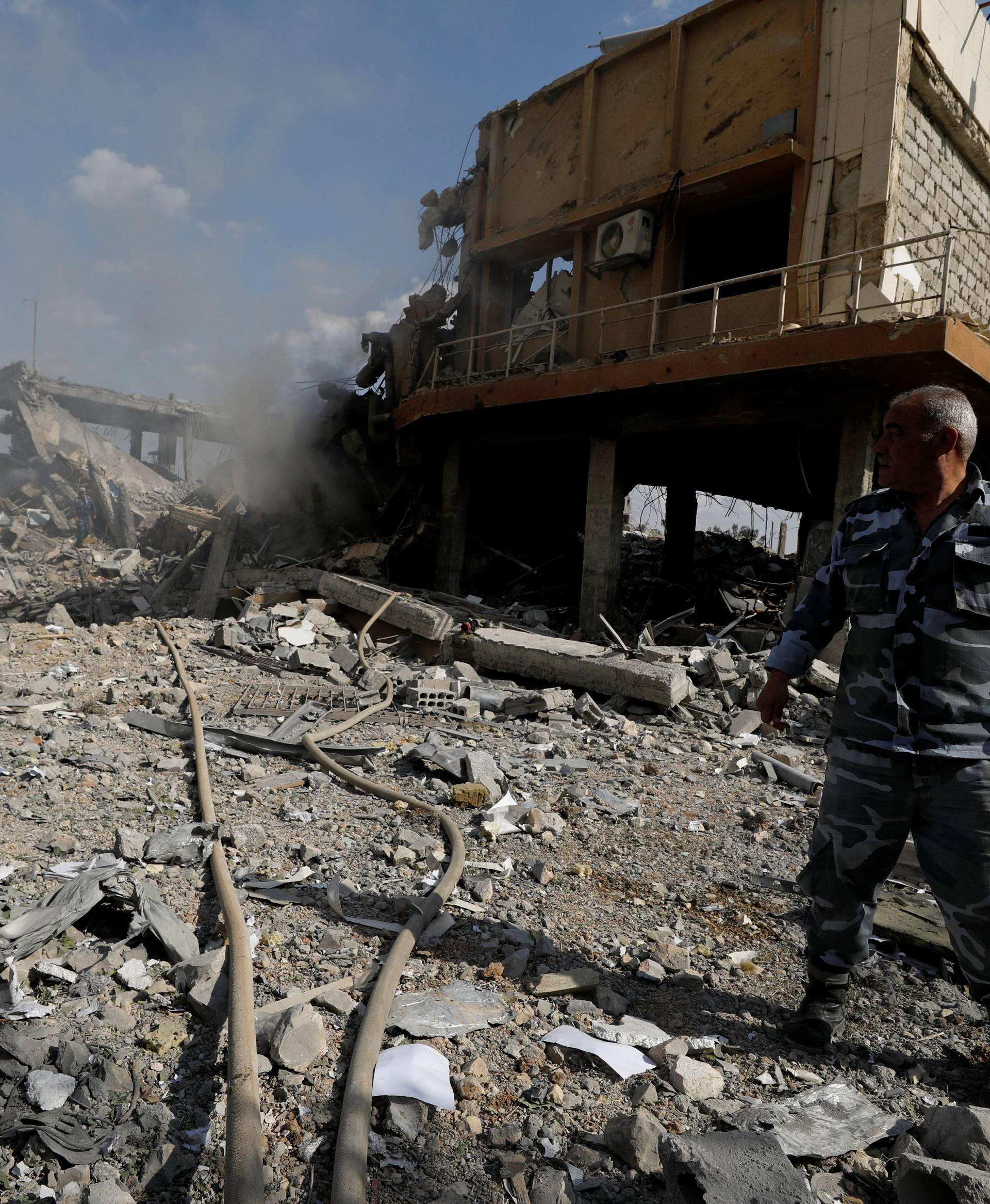 A Syrian firefighter is seen inside the destroyed Scientific Research Centre in Damascus