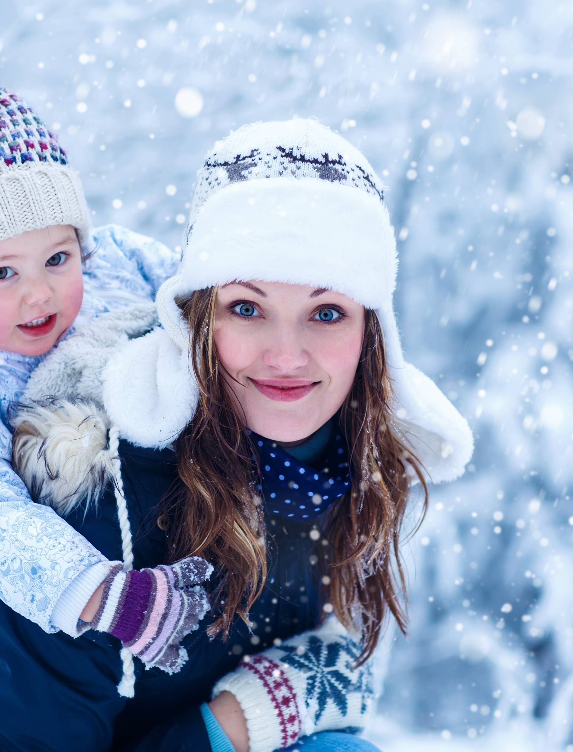 little girl and her mother in winter forest with snow