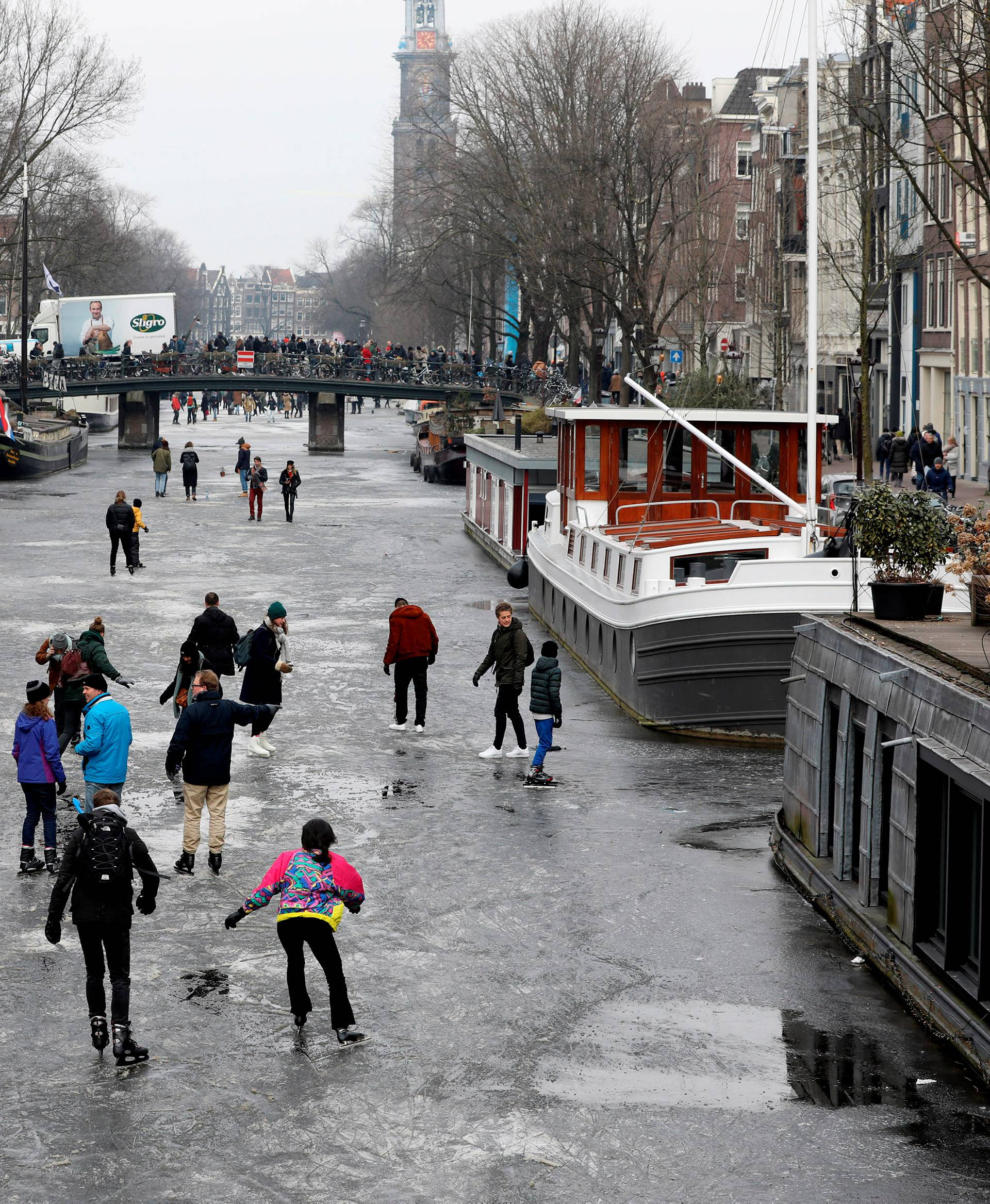 Ice skaters skate on the frozen Prinsengracht canal during icy weather in Amsterdam