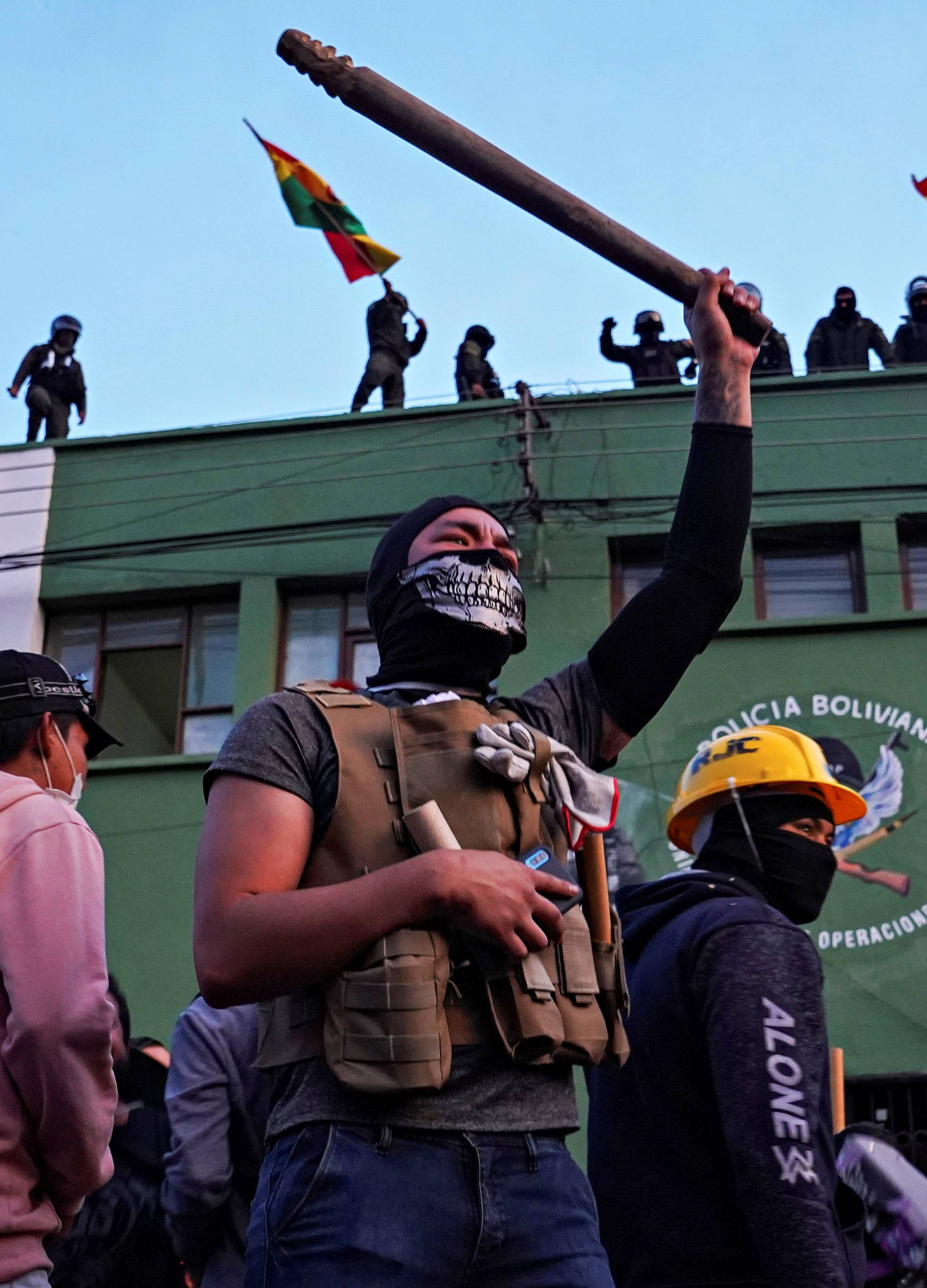 Opponents to Bolivia's President Evo Morales react as police officers stand on the roof of their headquarters, in Cochabamba