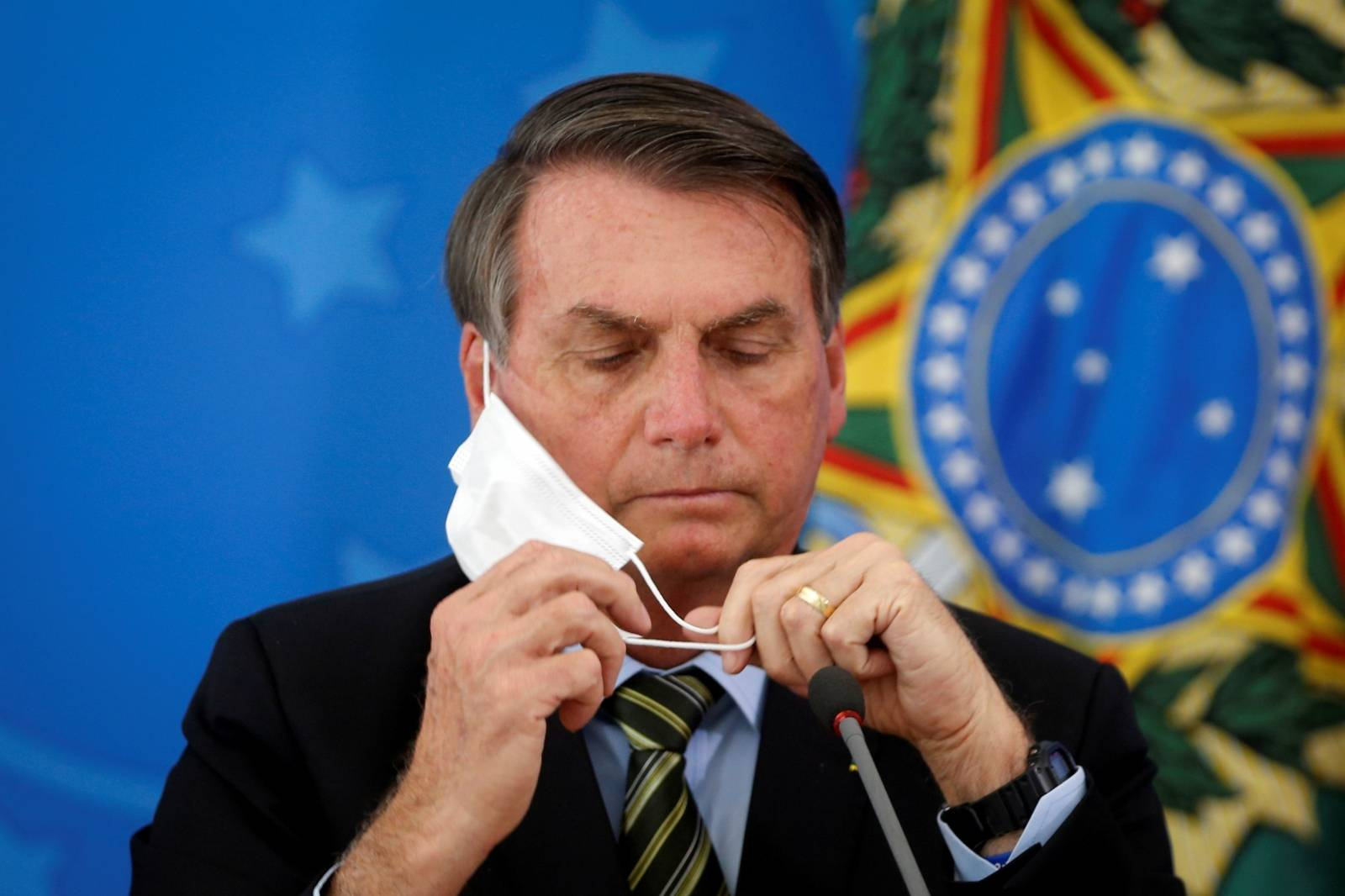 FILE PHOTO: Brazil's President Jair Bolsonaro adjusts his protective face mask during a press statement to announce federal judiciary measures to curb the spread of the coronavirus disease (COVID-19) in Brasilia