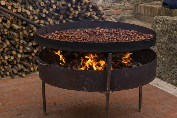 Roasting chestnuts in a large pan with a fire underneath in an historic hilltop town in Tuscany.