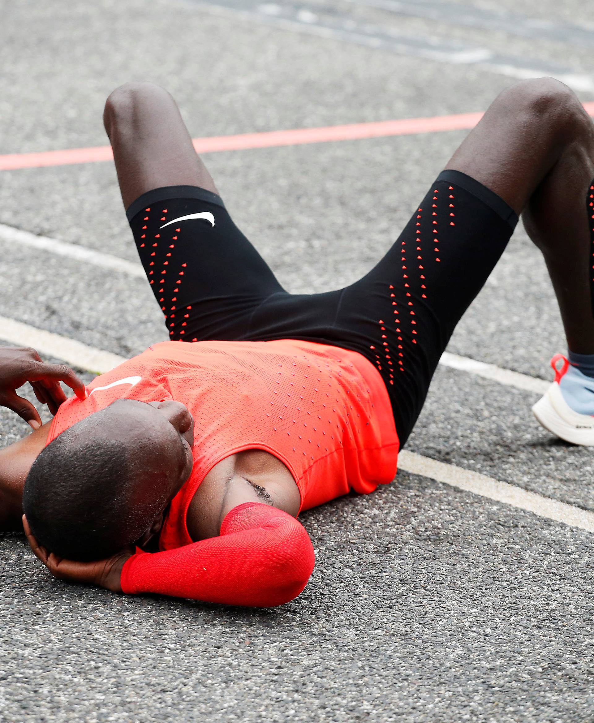 Kipchoge reacts after crossing  the finish line during an attempt to break the two-hour marathon barrier at the Monza circuit.