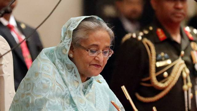Sheikh Hasina signs the official oath book after taking oath as the Prime Minister for the third consecutive time in Dhaka