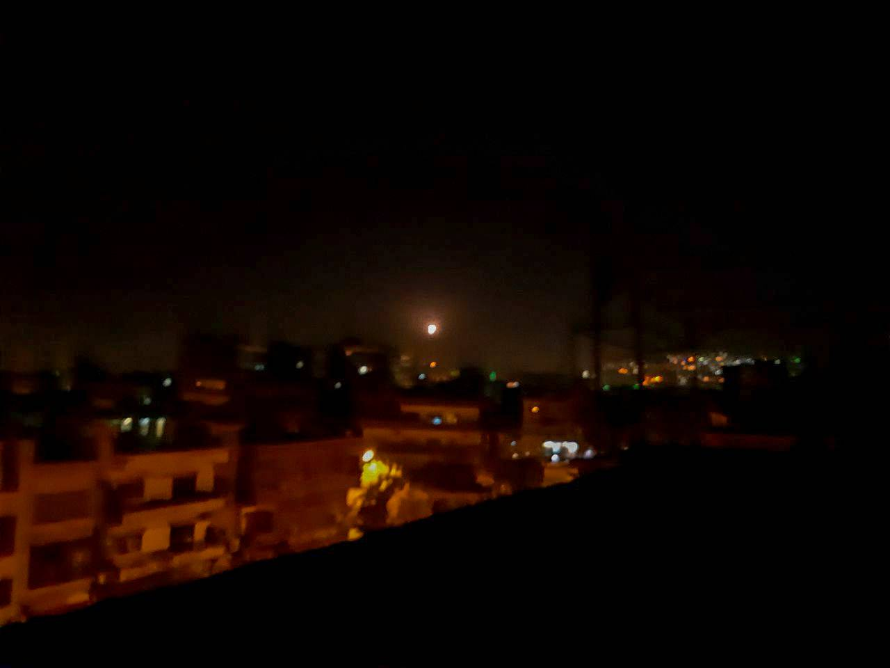 Light in the sky, believed to be a missile, is seen the city in Damascus