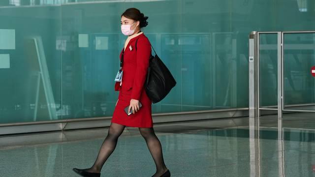 Cathay Pacific employee walks past the departures hall at Hong Kong International Airport in Hong Kong