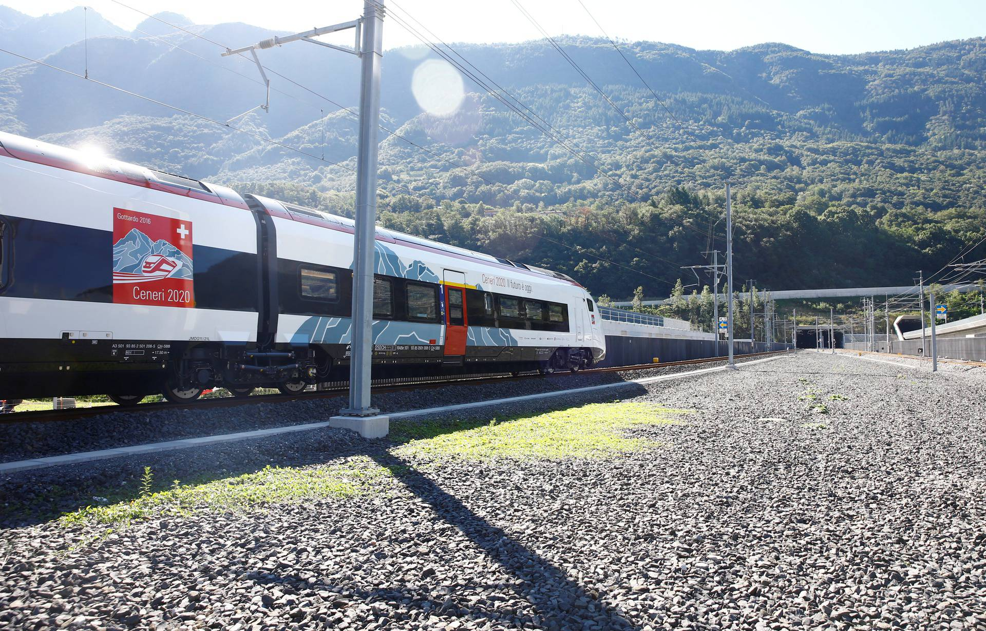 Train stands in front of the entrances of the newly built Ceneri Base Tunnel near Camorino