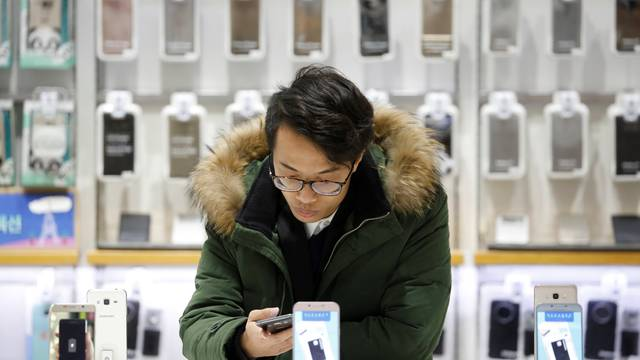 A man tries out a Samsung Electronics' smartphone at its store in Seoul