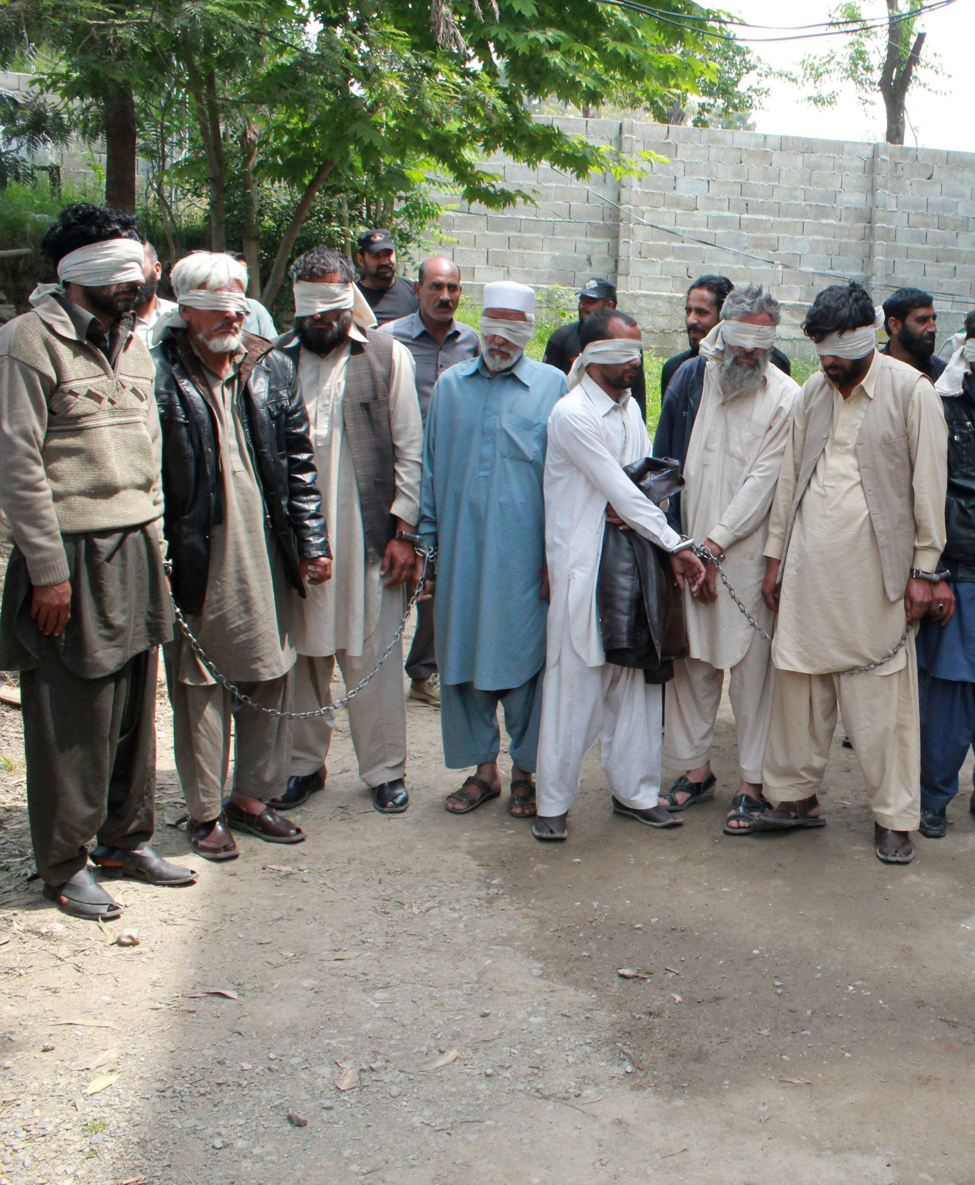Members of a tribal council accused of ordering the burning death of a 16 year old girl are shown to the media after they were arrested by police in Donga Gali, outside Abbottabad