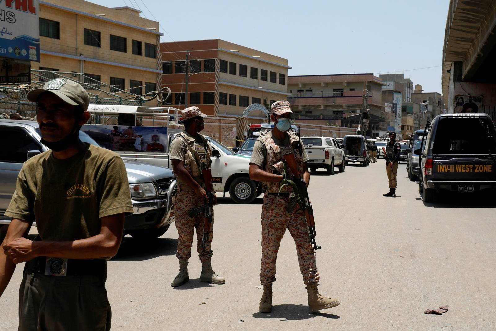 Paramilitary soldiers stand guard after a grenade blast outside a college, in Karachi