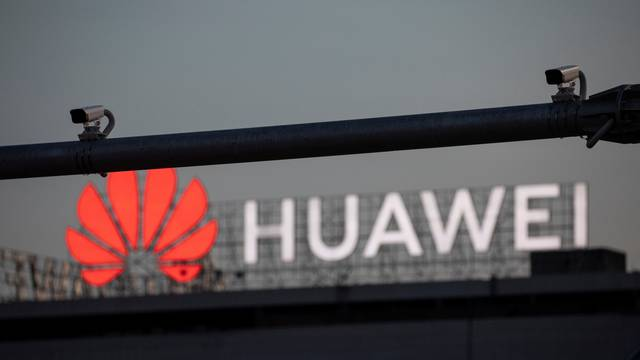 Surveillance cameras are seen in front of a Huawei logo in Belgrade