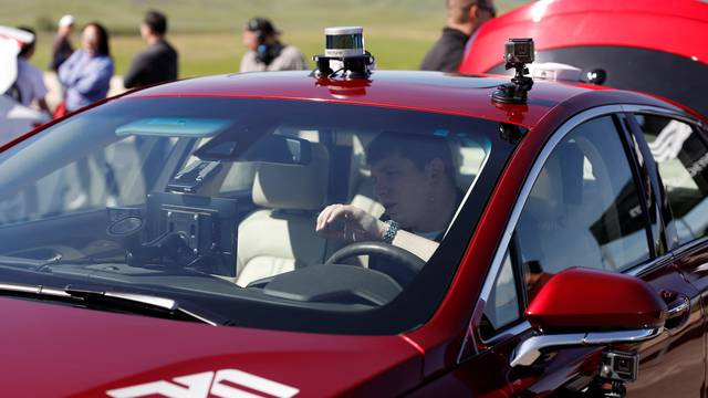 An engineer works on an AutonomouStuff Automated Research Development Vehicle during a self-racing cars event at Thunderhill Raceway in Willows, California