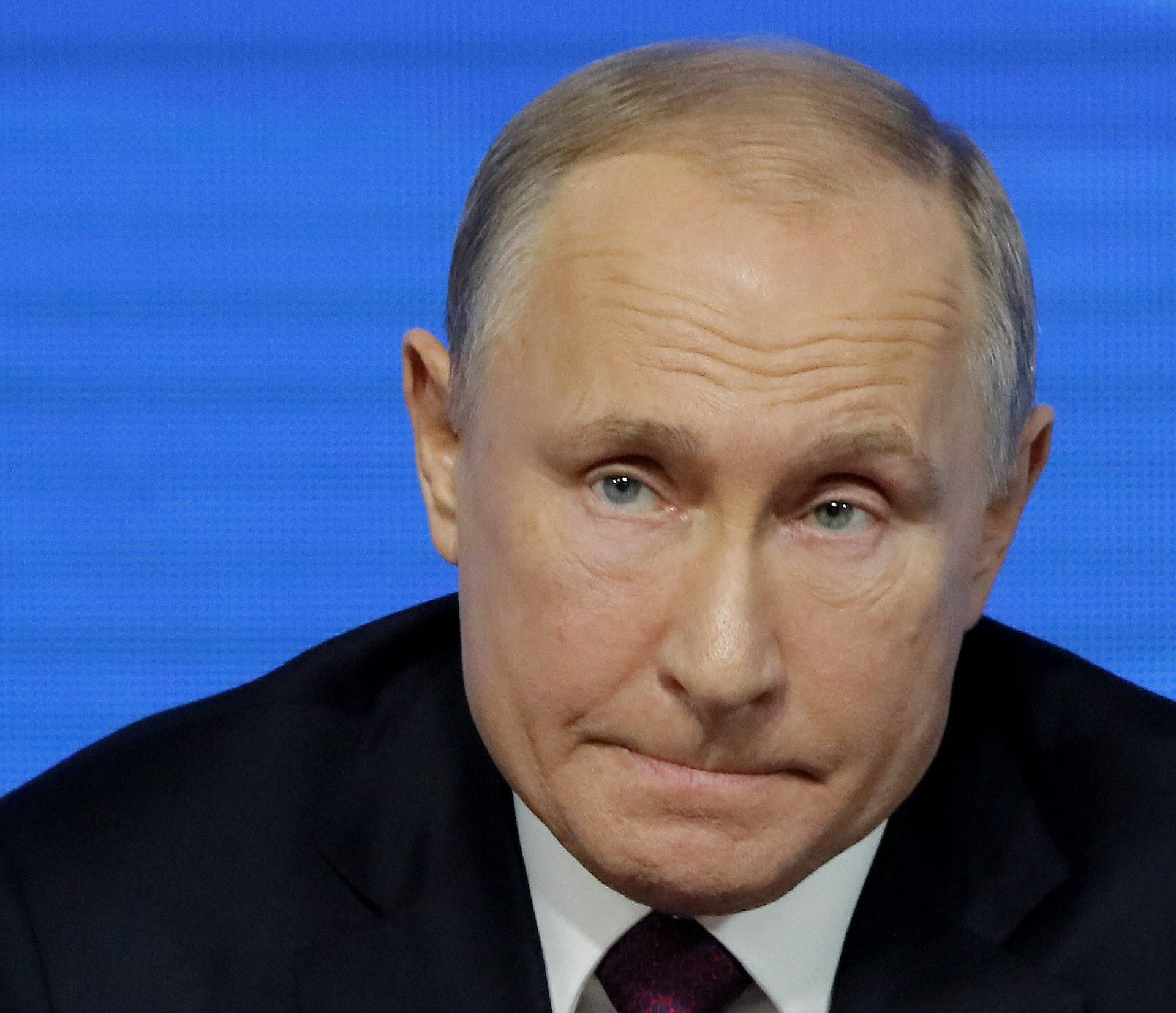 Russian President Putin listens during annual news conference in Moscow