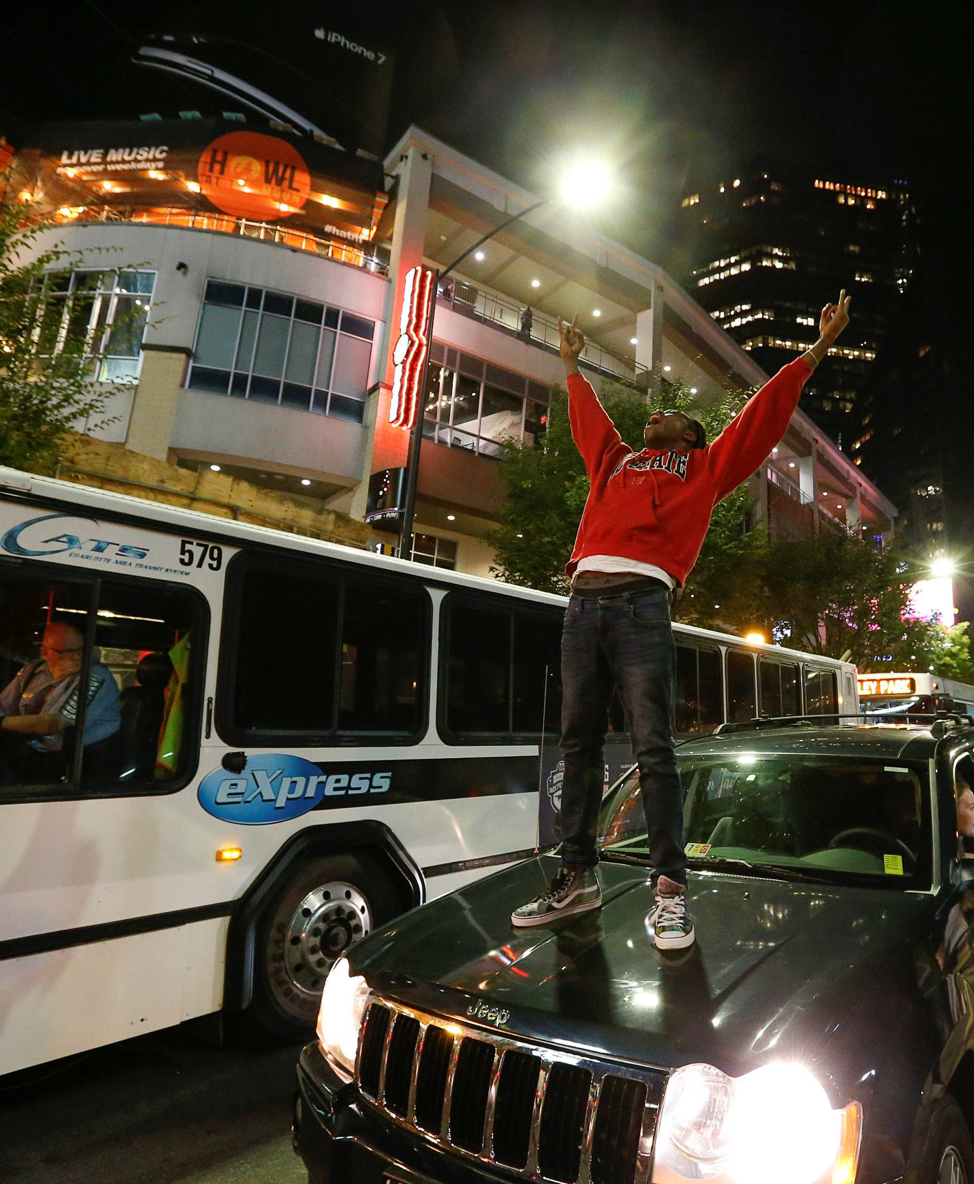 A man stands on a car in uptown Charlotte, NC to protest the police shooting of Keith Scott, in Charlotte, North Carolina