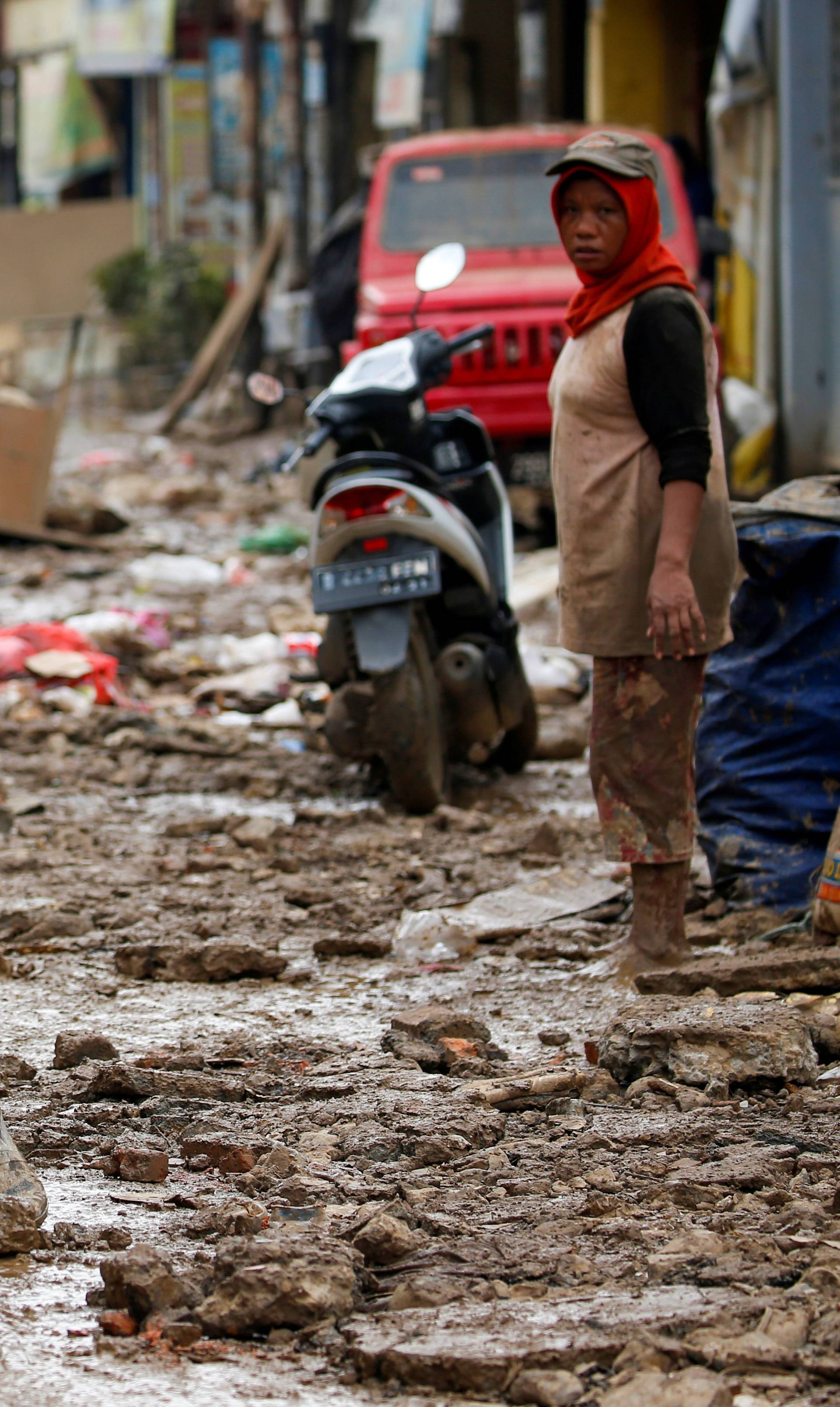 Man carrying a washing machine rides a motorbike as he collects items at a residential area affected by floods in Bekasi