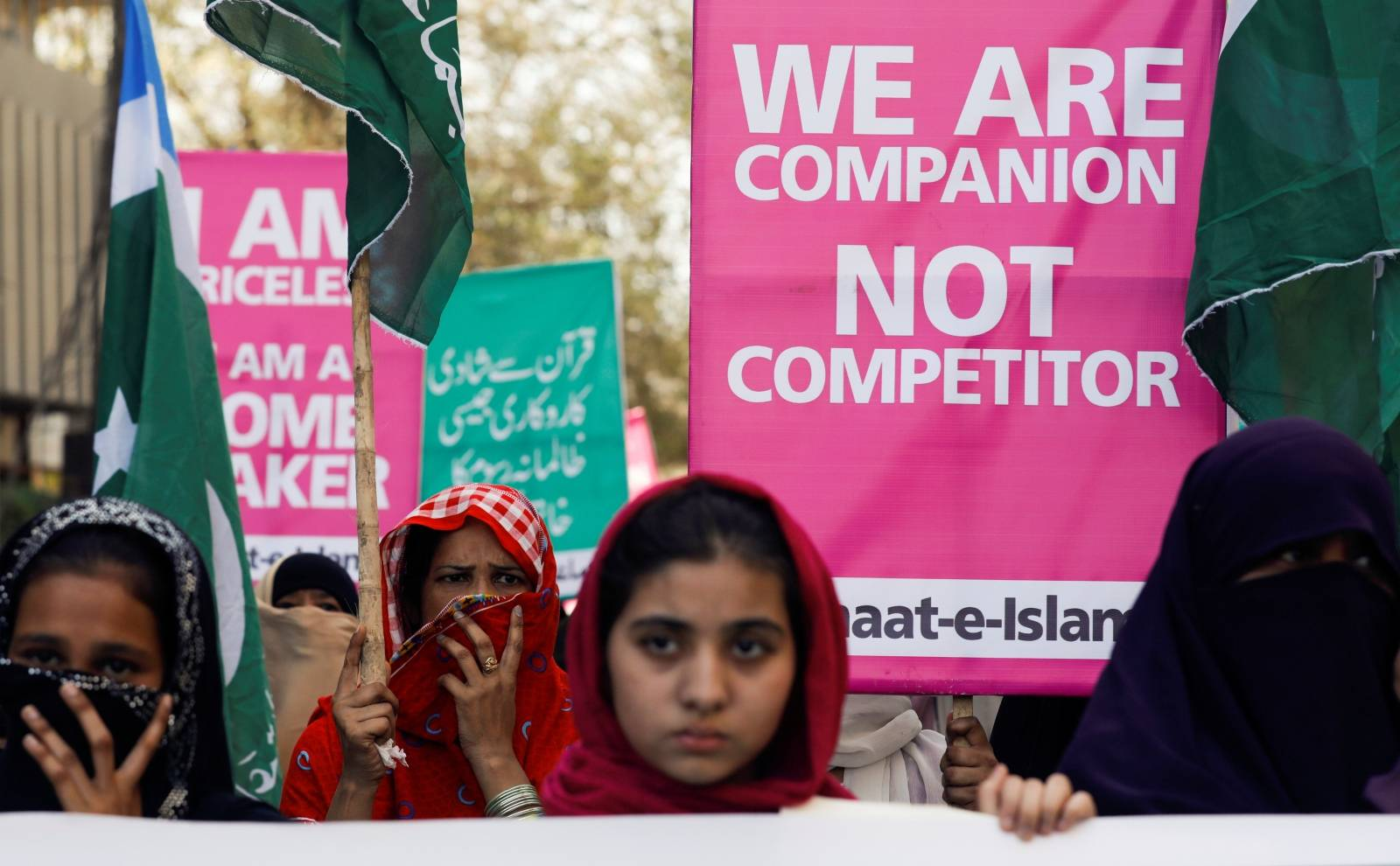 Women supporters of the religious and political party Jamaat-e-Islami (JI) hold signs as they take part in an Aurat March, or Women's March, in Karachi