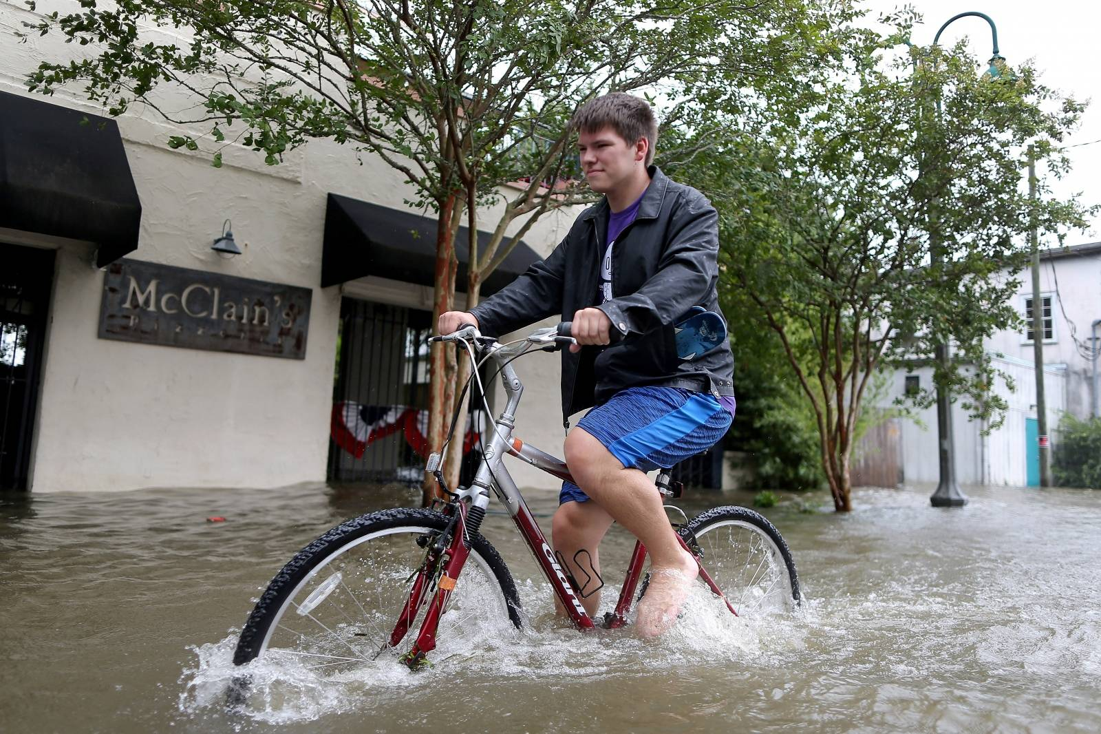 A resident bikes down a flooded street after Hurricane Barry in Mandeville