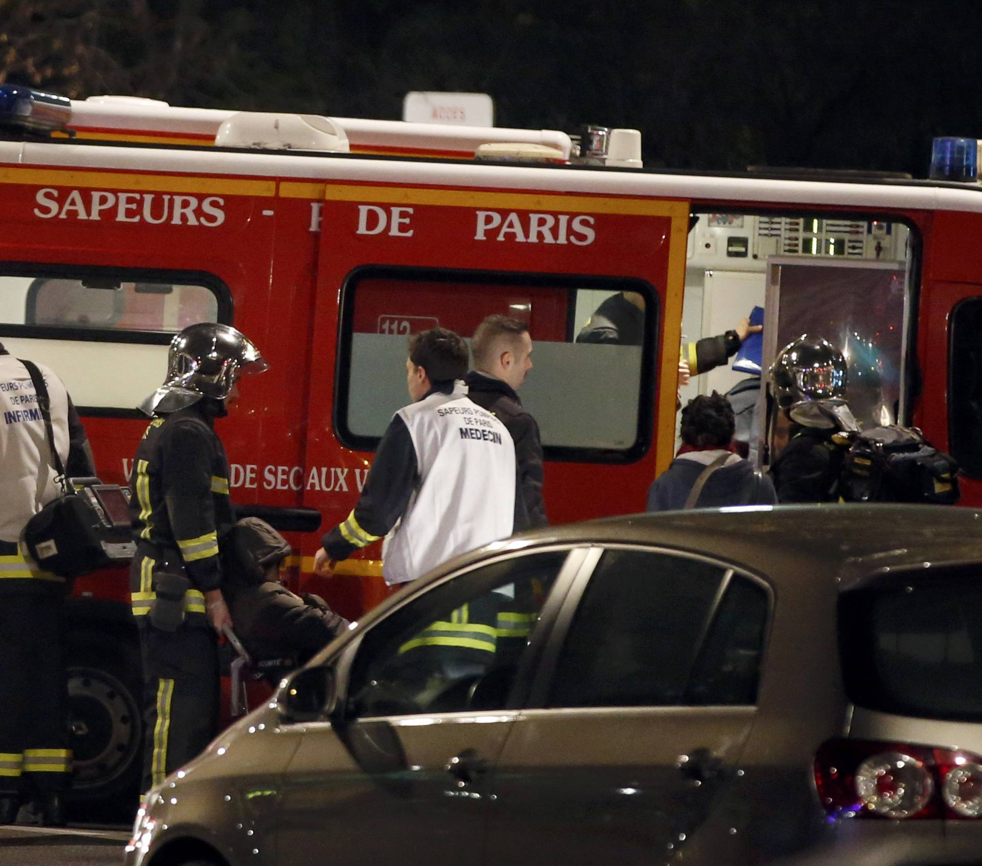 French firemen and doctors tend to a person who was one of six people in a travel agency when an armed man entered in what appears to be a robbery, according to a police source, in Paris