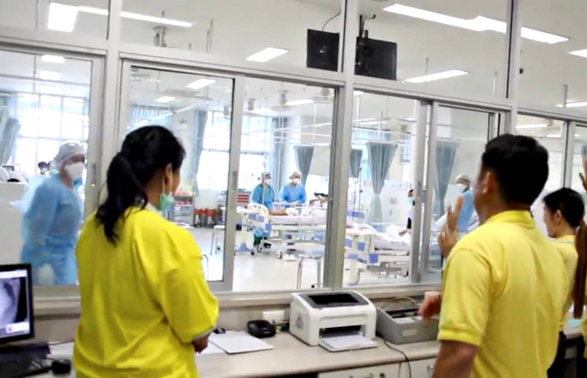 FILE PHOTO: A screen grab shows people looking through glass at the boys rescued from the Thai cave at a hospital in Chiang Rai
