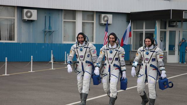 The International Space Station (ISS) crew members walk before leaving to board the Soyuz MS-16 spacecraft for the launch at the Baikonur Cosmodrome