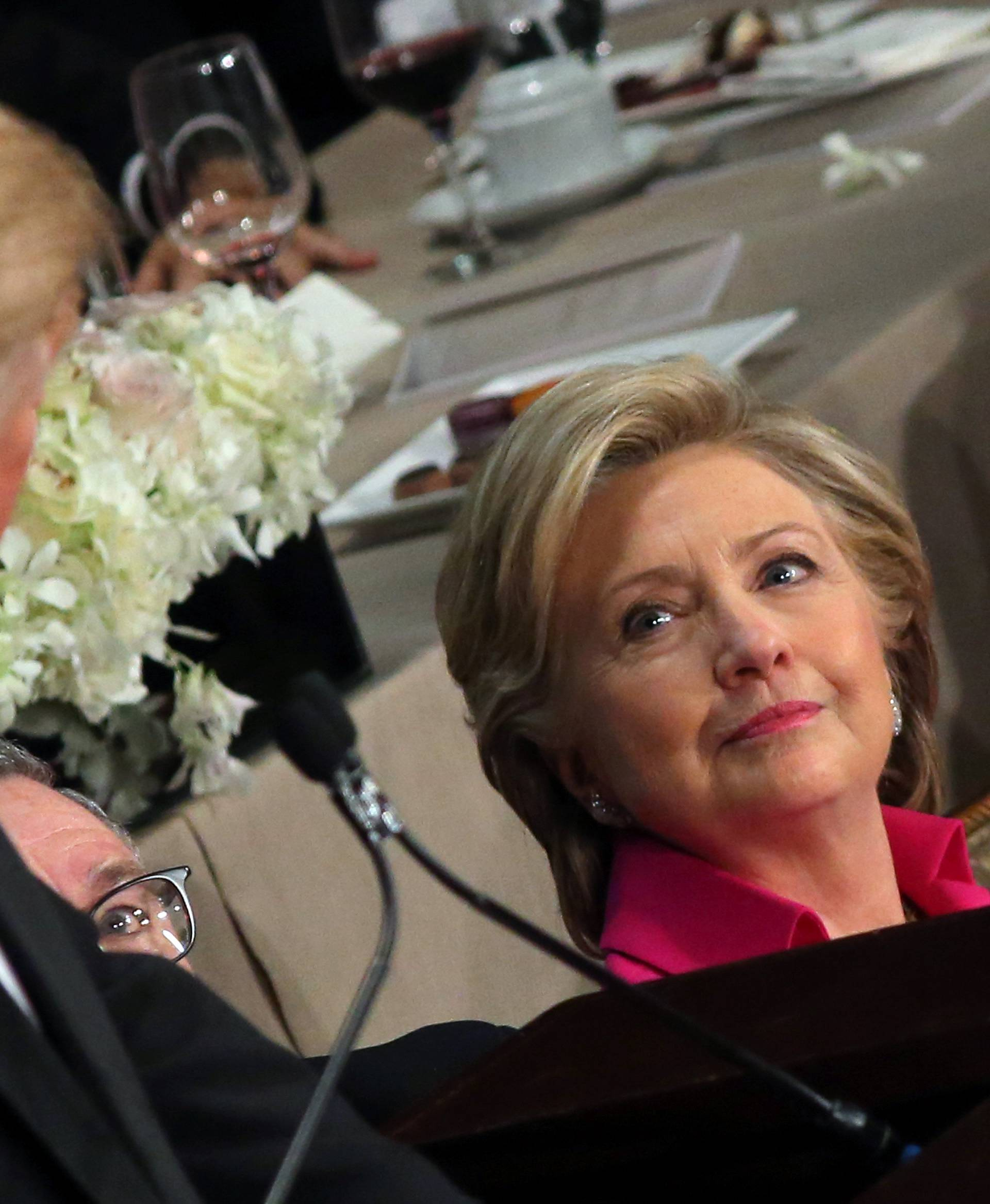 Democratic U.S. presidential nominee Hillary Clinton looks at Republican U.S. presidential nominee Donald Trump as he speaks during the Alfred E. Smith Memorial Foundation dinner in New York, U.S.