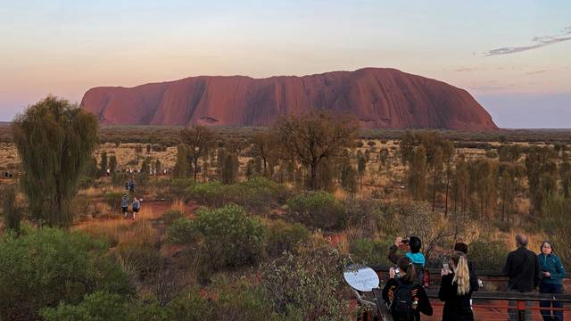 People view Uluru, the day before a permanent ban on climbing the monolith takes effect following a decades-long fight by indigenous people to close the trek, near Yulara