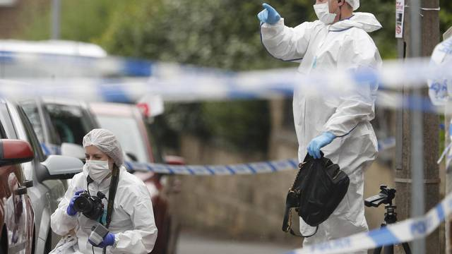 A forensic police officer collects a handbag from the ground behind a police cordon in Birstall near Leeds