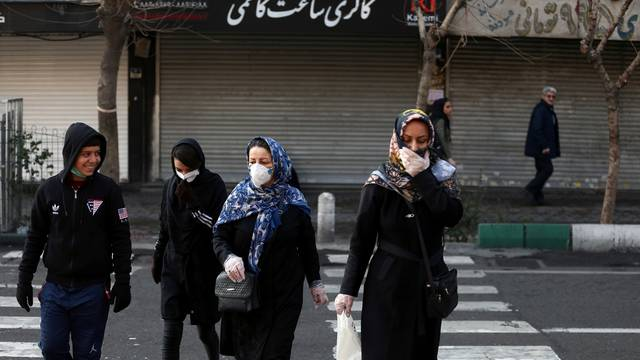Iranian people wear protective masks to prevent contracting a coronavirus, in Tehran