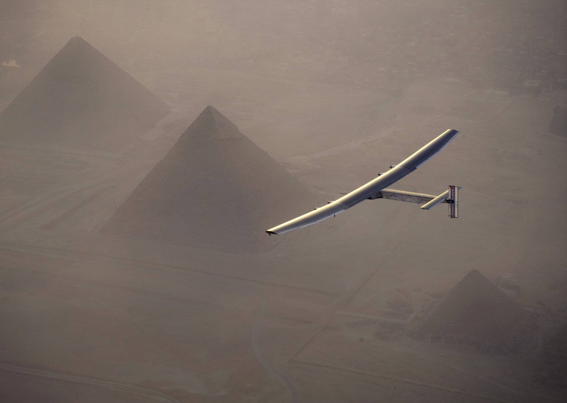 Solar Impulse 2, the solar powered plane, piloted by Swiss pioneer Andre Borschberg is seen during the flyover of the pyramids of Giza on July 13, 2016 prior to the landing in Cairo
