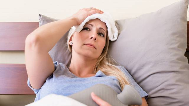 Young sick woman with fever lying in bed