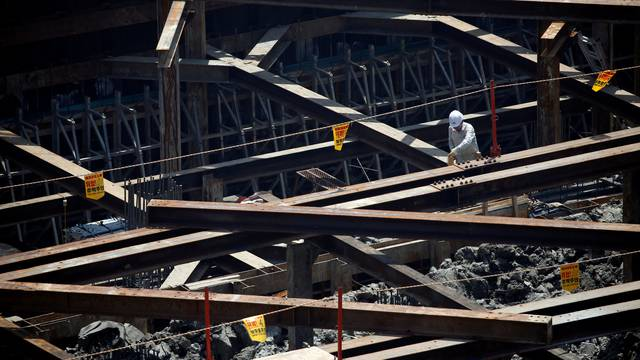 Labourers work at a construction site in Seoul