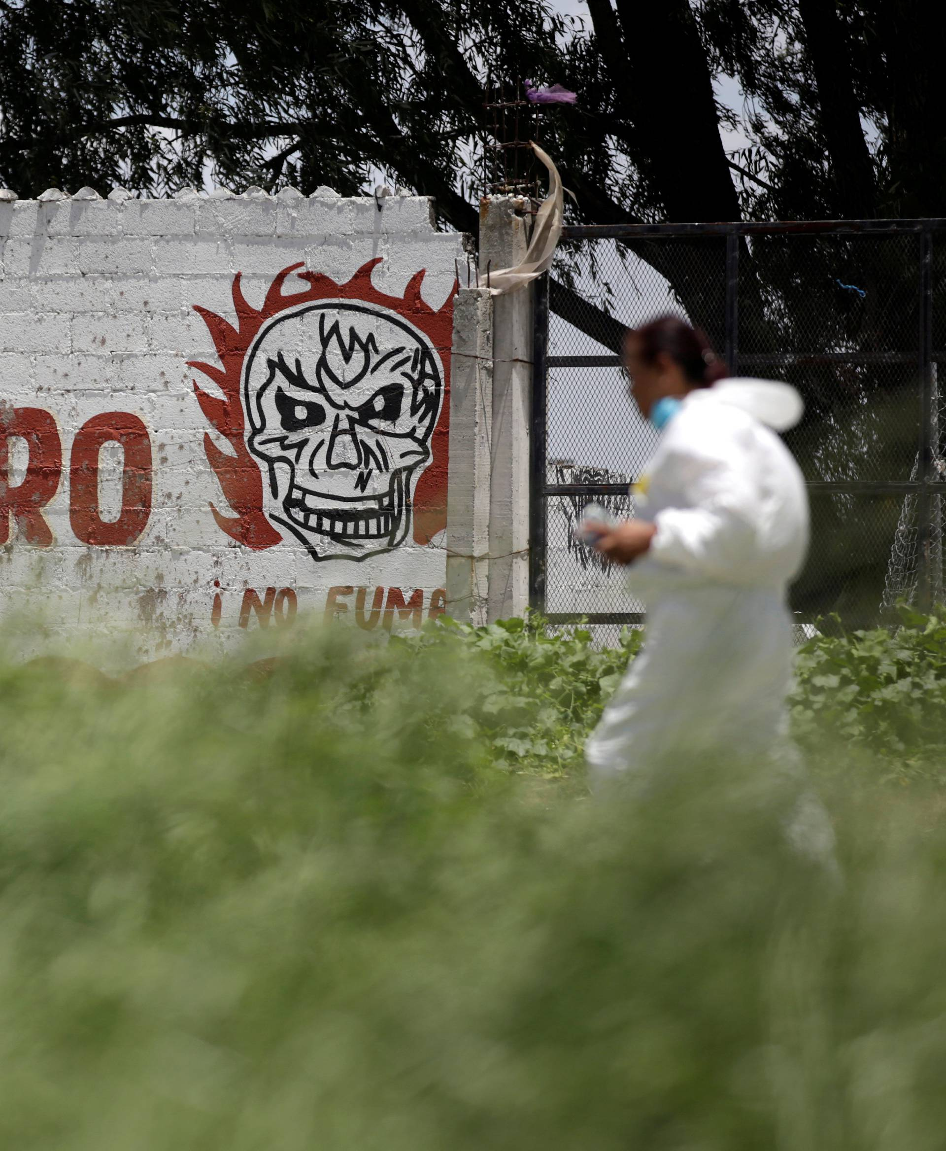 """A forensic technician walks by a wall reading """"Danger"""" while inspecting a site damaged due to fireworks explosions in the municipality of Tultepec"""